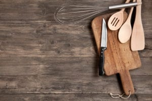 Kitchen utensils on an old wooden background